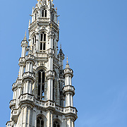 Spire of the Town Hall in the Grand Place, Brussels. Originally the city's central market place, the Grand-Place is now a UNESCO World Heritage site. Ornate buildings line the square, including guildhalls, the Brussels Town Hall, and the Breadhouse, and seven cobbelstone streets feed into it. The spire is set against a clear blue sky.