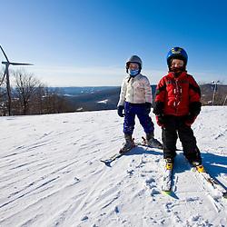 Two young skiers at Jiminy Peak ski resort in the Berkshire Mountains in Hancock, Massachusetts.  Wind turbine.