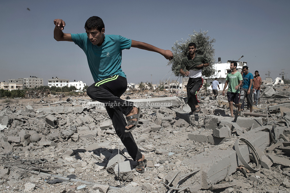 Gaza Strip, Khuza'a: During a 72 hours shortly broken ceasefire Palestinians rush to their homes in Khuza'a to retrieve their belongings on August 1, 2014. ALESSIO ROMENZI