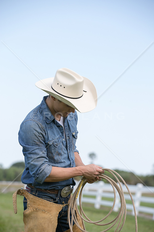 All American Cowboy with a lasso on a beautiful ranch
