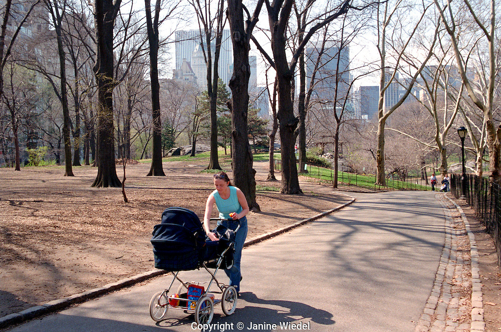 Mother with baby in pram walking in Central Park.