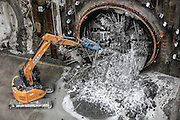 An excavator helps pull away debris from tunnel-boring machine Brenda after it broke through the last few feet of the light-rail tunnel segment from Northgate to the University District Station. (Steve Ringman / The Seattle Times)