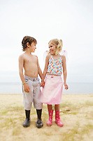 Boy and girl standing on beach holding hands portrait