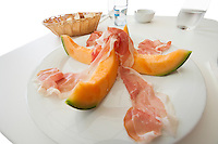 Melon slices with meat served on plate