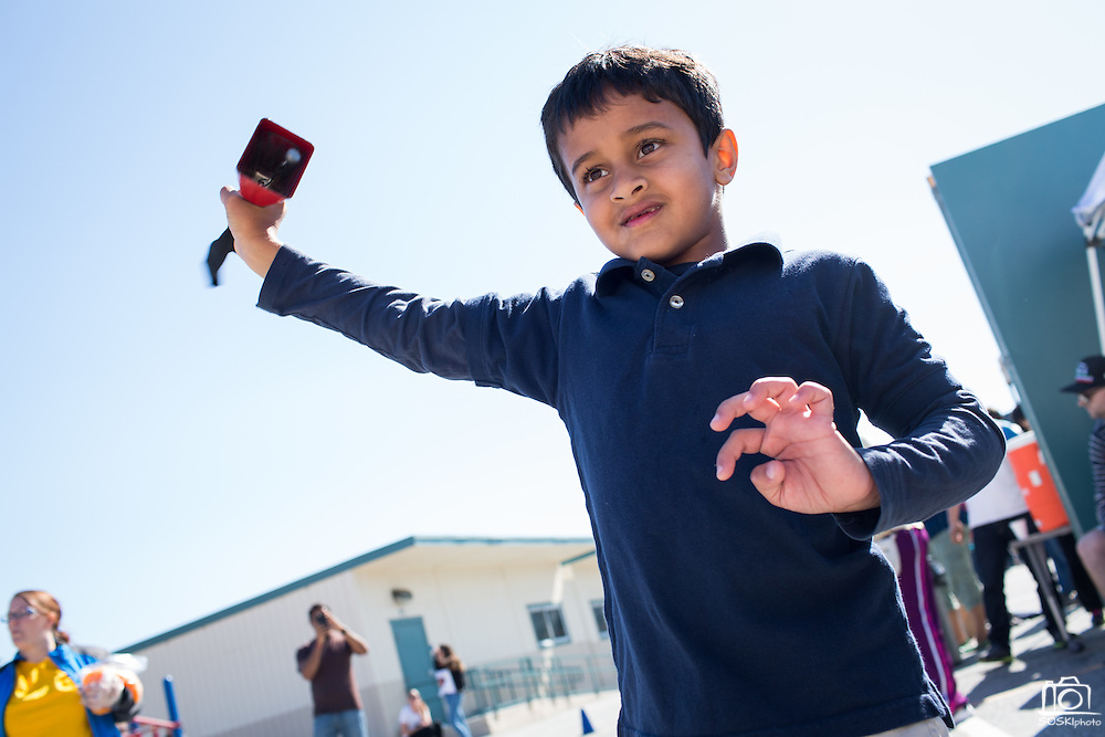 Kindergartener Akshat Giri rings a cowbell to mark the final lap during a Run for Fun fundraiser at Zanker Elementary School in Milpitas, California, on April 30, 2016. (Stan Olszewski/SOSKIphoto)