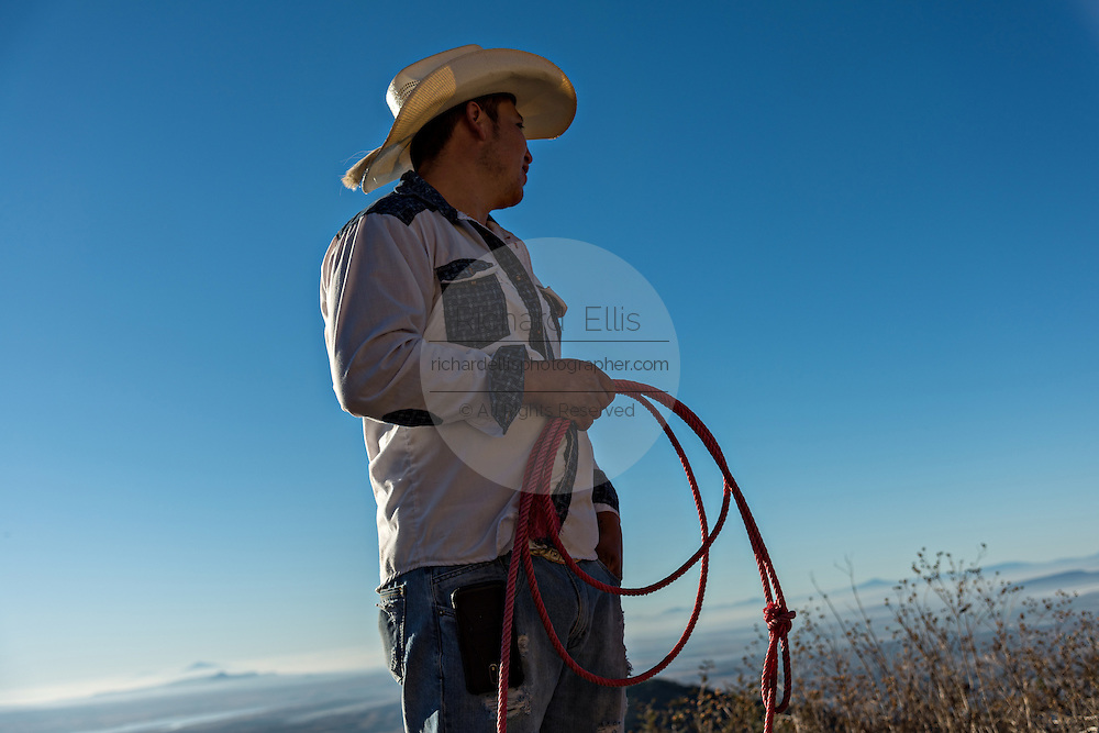 A Mexican cowboy looks at the view as he breaks camp on Cubilete Mountain at the start of the final day during the annual Cabalgata de Cristo Rey pilgrimage January 6, 2017 in Guanajuato, Mexico. Thousands of Mexican cowboys and horse take part in the three-day ride to the mountaintop shrine of Cristo Rey.