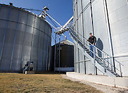 Rick Elliott stands on the stairs leading to the top of a 200,000 bushel grain bin on his farm in Monmouth, Illinois on Friday, February 17, 2012. On the left is a 100,000 bushel grain bin.