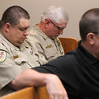 Prentiss County Sheriff Deputy Dennis Peeks joins other deputies as they pray during Wednesday's law enforcement memorial service at the Prentiss County Justice Court in Booneville.