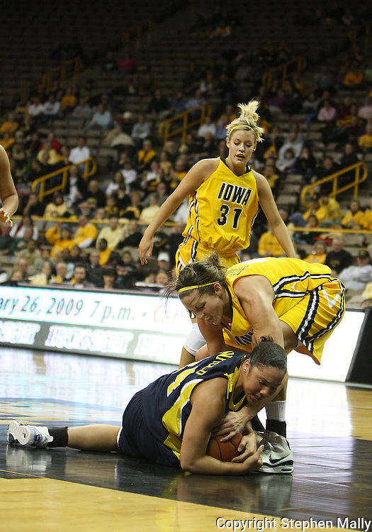 26 JANUARY 2009: Michigan guard Jessica Minnfield (34) battles with Iowa forward Wendy Ausdemore (32) for a lose ball while Iowa guard/forward Hannah Draxten (31) looks on during the first half of an NCAA women's college basketball game Monday, Jan. 26, 2009, at Carver-Hawkeye Arena in Iowa City, Iowa. Iowa defeated Michigan 77-69.