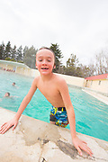 Little boy smiling while climbing out of the pool during family fun swimming at Banbury Hot Springs in Hagerman, Idaho. MR