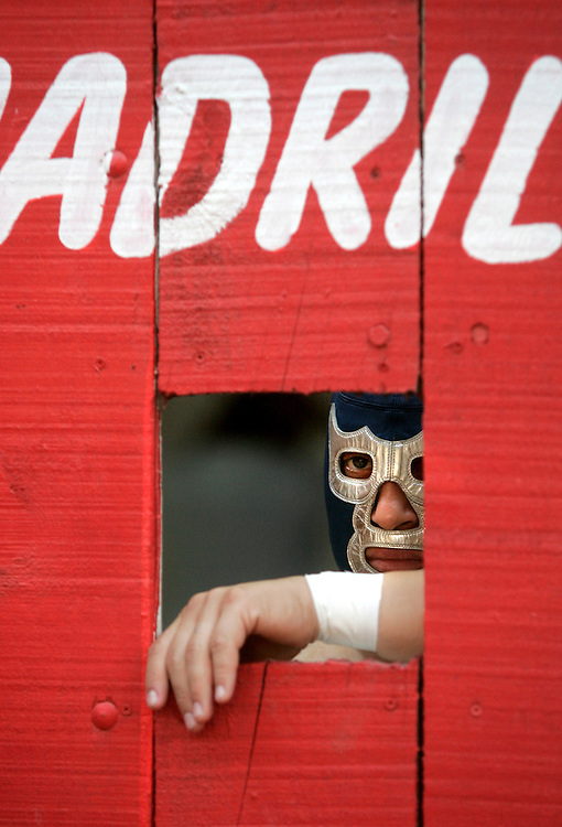 Blue Demon Jr. watches the opening rounds of a Lucha Libre match in Reynosa's Plaza de Toros from behind the arena's entry doors.  The son of famed wrestler Blue Demon, he shares his father's instantly recognizable blue and silver mask.