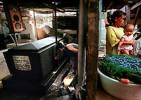 Arminda Hilario, left, washes one of two tombs that rest within the walls of her shanty home. Her husband s fishing nets sit outside the house where Hilario s neighbors congregate.  About 200 families live near or among the graves in Cavite City Cemetery.  Although the conditions are grim based on U.S. standards, for the poor in the Philippines free rent, a neighboring dump and Manila Bay offer the promise for a livable income.(Janet Jensen/The News Tribune)