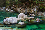 Large boulders sit in the emerald green pools in Gold Creek at Golden Ears Provincial Park, Maple Ridge, British Columbia, Canada. The colour here is from minerals suspended in Gold Creek's water from its journey down from the Coast Mountains.  Photographed from along the North Beach Trail to the mouth of Gold Creek at Alouette Lake.