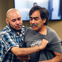 A family member pulls Rafael Muniz of Virginia, right, from a courtroom Friday where a bond hearing was held for Dennis Elvin Cervantes Pavon, accused of fatally stabbing Muniz's son, Raymond Muniz, on Wednesday in Mount Pleasant. (ANDREW KNAPP/STAFF)