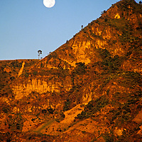 Americas, Central American, Guatemala, Lake Atitlan. A full moon rises over the volcanic peaks of Lago Atitlan in Guatemala.