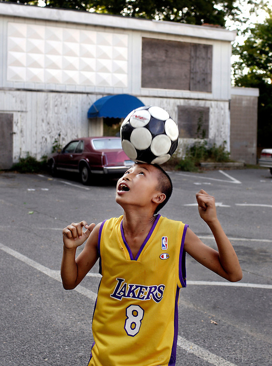 Karen refugee Lay Moo, 14, bounces a soccer ball on his head while playing in the parking lot of the apartment complex he lives in in Waterbury. Lay Moo had just recently arrived in the United States when this photo was taken on October 10, 2007.  .(Photo by Robert Falcetti)
