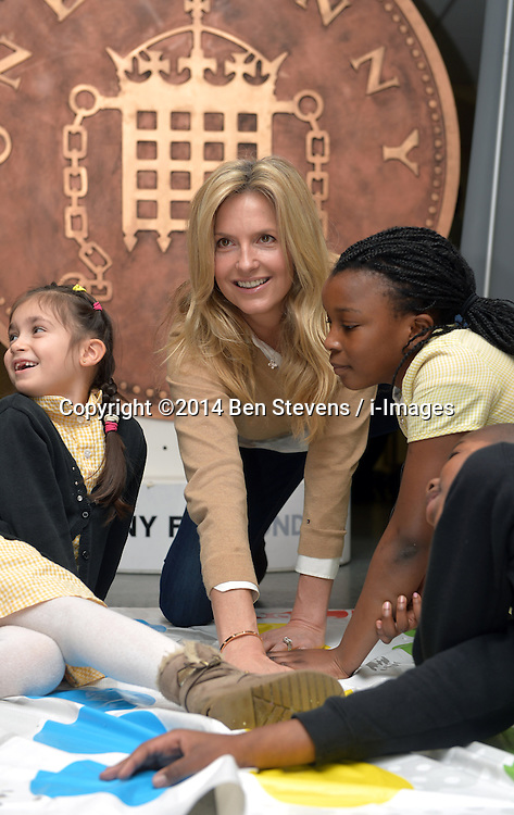 Image &copy;Licensed to i-Images Picture Agency. 18/12/2014. London, United Kingdom. <br /> <br /> Penny Lancaster visits Charlton Manor Primary School where the Mayors Fund initiative 'Penny for London' is raising money to fund breakfasts for school children.<br /> <br /> Penny Lancaster plays twister during breakfast club.<br /> <br /> Picture by Ben Stevens / i-Images