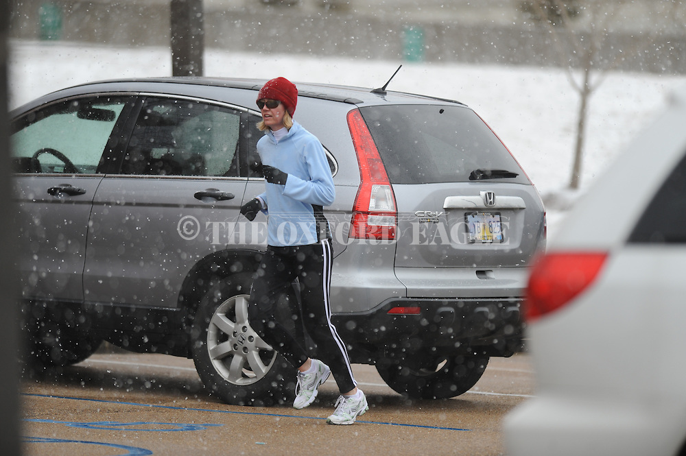 A woman runs in the snow on Monday, February 15, 2010 in Oxford, Miss.