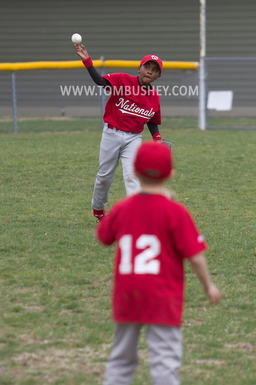 Montgomery , New York - One player throws the ball to another player between innings of a Little League baseball game  on April 13, 2013.