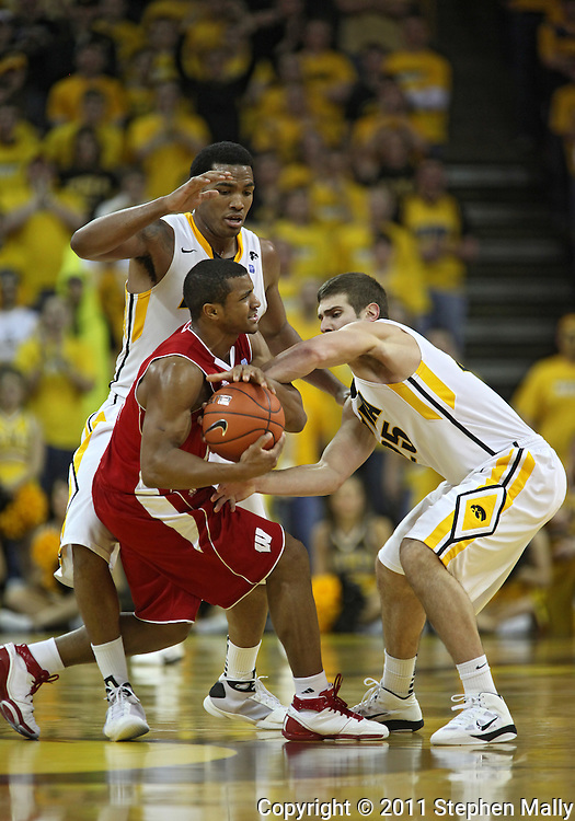 February 09 2011: Wisconsin Badgers guard Jordan Taylor (11) tries to keep the ball away from Iowa Hawkeyes forward Jarryd Cole (50) and Iowa Hawkeyes guard/forward Eric May (25) during the second half of an NCAA college basketball game at Carver-Hawkeye Arena in Iowa City, Iowa on February 9, 2011. Wisconsin defeated Iowa 62-59.