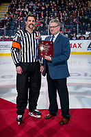 KELOWNA, BC - NOVEMBER 30:  WHL Senior Director, Officiating, Kevin Muench presents a milestone award to referee Steve Papp for officiating 650 career games at the start of the game between the Kelowna Rockets and the Prince George Cougars at Prospera Place on November 30, 2019 in Kelowna, Canada. (Photo by Marissa Baecker/Shoot the Breeze)