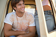 Young man sitting in van doorway young woman standing mid section