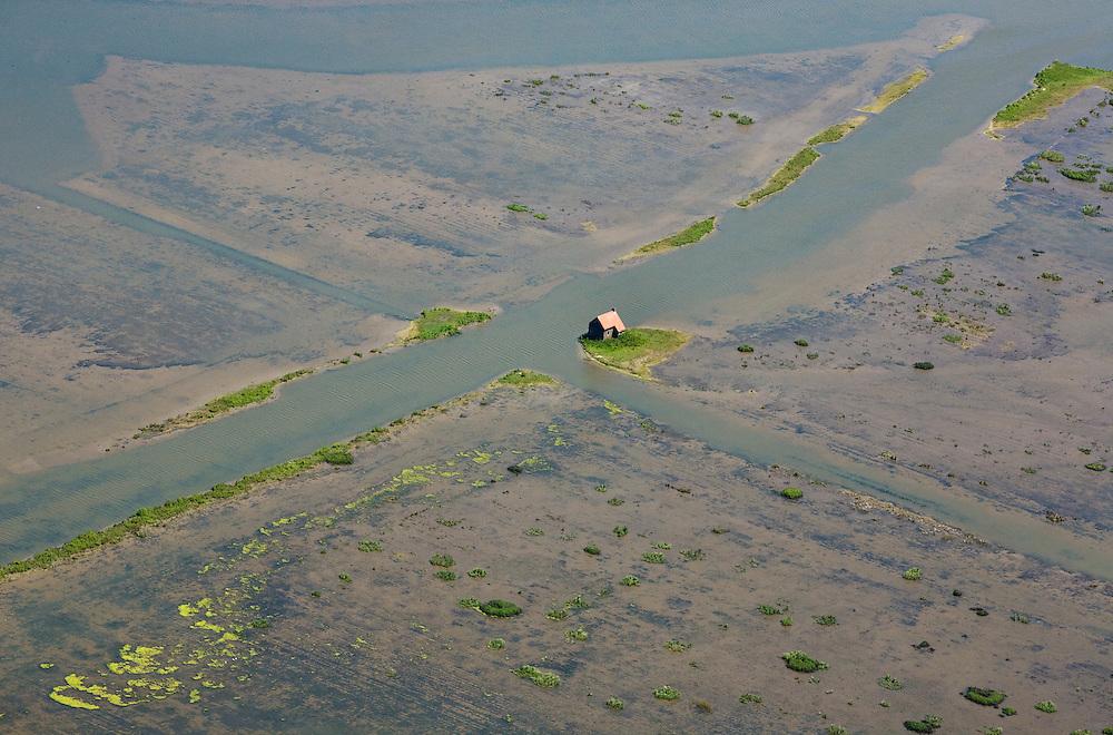 """Nederland, Zuid-Holland, Tiengemeten, 12-06-2009; overgebleven huisje op eiland in het Haringvliet, detail van het ondergelopen deel van het eiland. Oorspronkelijk gebruikt voor de akkerbouw maar inmiddels 'teruggegeven aan de natuur', de dijken zijn deels doorgestoken, de laatste boer is in 2006 vertrokken. Huidig gebruik onder andere zorgboerderij en kan er gekampeerd worden. De 'nieuwe natuur' vormt onderdeel van de Ecologische Hoofdstructuur. Oorspronkelijk was het eilandje eigendom van AMEV (Fortis Investments) - binnen de dijken, de buitendijkse slikken waren van de Vereniging Natuurmonumenten..The island Tiengemeten in the Haringvliet, originally owned - within the dikes - by AMEV (Fortis Investments), and Natuurmonumenten (Society for conservation of nature). The island was used for agriculture but has now """"been given back to nature"""", large parts have been flooded and the isle is part of the National Ecological Network. The last farmer left in 2006. Current use, among other, care farms and camping..Swart collectie, luchtfoto (25 procent toeslag); Swart Collection, aerial photo (additional fee required).foto Siebe Swart / photo Siebe Swart"""