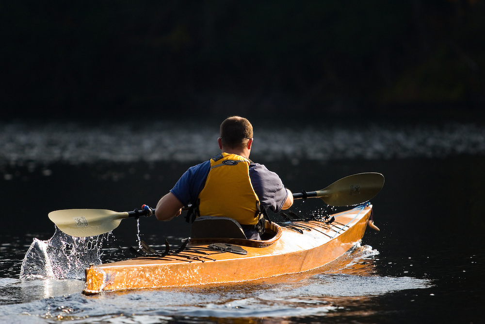 A man paddling a sea kayak accross Otter Lake in the Adirondacks, New York State