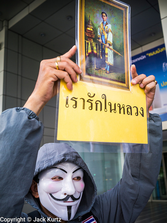 "09 JUNE 2013 - BANGKOK, THAILAND:  A White Mask protester holds up a photo of Bhumibol Adulyadej, the King of Thailand, during an anti-government protest. The White Mask protesters are ultra royalists who support the King and wear the Guy Fawkes mask popularized by the movie ""V for Vendetta"" and the protest groups Anonymous and Occupy. Several hundred members of the White Mask movement gathered on the plaza in front of Central World, a large shopping complex at the Ratchaprasong Intersection in Bangkok, to protest against the government of Thai Prime Minister Yingluck Shinawatra. They say that her government is corrupt and is a ""puppet"" of ousted (and exiled) former PM Thaksin Shinawatra. Thaksin is Yingluck's brother. She was elected in 2011 when her brother endorsed her.    PHOTO BY JACK KURTZ"