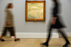 "© Licensed to London News Pictures. 14/06/2019. LONDON, UK. Staff members walk by ""Nymphéas"", 1908, by Claude Monet (Est. £25-30m). Preview of Impressionist and Modern art sales, which will take place at Sotheby's New Bond Street on 18 and 19 June 2019.  Photo credit: Stephen Chung/LNP"