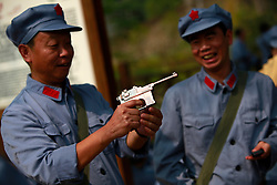 Chinese communist party course trainees dressed in Red Army uniforms play with a souvenir gun outside a former residence of Mao Zedong in Jinggangshan of Jiangxi Province, China, 16 October 2012.  Jinggangshan or Jinggang mountain is a popular destination for Red Tourism where Chinese communist party cadres and ordinary Chinese tourists alike converge, seeking to relive the experiences and rekindle the spirit of the revolutionaries. It is deemed as the birthplace of the Chinese Red Army and the 'cradle of the Chinese revolution' which saw Communist leader Mao Zedong's ascent to power as a revolutionary. After a failed uprising in 1927, Mao fled into the mountains with his 1,000 remaining troops from nationalist forces and set up base here to reorganize his army, eventually defeating the Kuomingtang (KMT) to rule the country. Cadres dressed in Red Army uniforms attending Communist party training courses in are a common sight in the various historical sites of the mountain where they sing red songs and retrace the paths taken by their forbears. The Chinese communist party is slated to hold its 18th national congress on 08 November where a major leadership transition will see current leaders President Hu Jintao and Premier Wen Jiabao make way for a new generation of leaders helmed by Xi Jinping, With more than 80 million members, the Chinese Communist Party is hard pressed to display a show of unity and power after  scandals the ousting of disgraced politician Bo Xilai roiled the country. .