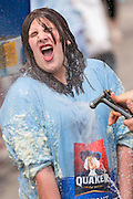 Contestants covered in sticky grits are washed off during the World Grits Festival rolling in the grits contest April 12, 2014 in St. George, South Carolina. Contestants have to roll in a vat of grits and the one with the most grits sticking to their body wins. Grits are a tradition Southern dish of thick maize-based porridge made from dried corn hominy.