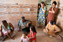 © Licensed to London News Pictures. Hamdaniyah, Iraq. 25/07/2014. Hamdaniyah, Iraq.Some of the members of a 17 strong Iraqi Christian refugee family gather in the kitchen of the unfinished house they now inhabit in Hamdaniyah, Iraq. The family all left Mosul on Friday the 18th of July when Islamic State fighters issued an ultimatum to the city's Christian community. When the family left they were forced to pay a tax for their car, and one member was threatened at knifepoint to ensure they handed over all of their possessions.<br /> <br /> Having taken over Mosul Iraq's second largest city in June 2014, fighter of the Islamic State (formerly known as ISIS) have systematically expelled the cities Christian population. Despite having been present in the city for more than 1600 years, Christians in the city were given just days to either convert to Islam, pay a tax for being Christian or leave; many of those that left were also robbed at gunpoint as they passed through Islamic State checkpoints.. Photo credit : Matt Cetti-Roberts/LNP