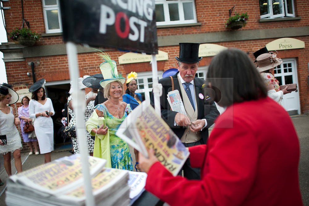 © London News Pictures. 20/06/2013. Ascot, UK.  Racegoers buying the racing post as they queue to enter the racecourse for Ladies Day on day three of Royal Ascot at Ascot racecourse in Berkshire, on June 20, 2013.  The 5 day showcase event,  which is one of the highlights of the racing calendar, has been held at the famous Berkshire course since 1711 and tradition is a hallmark of the meeting. Top hats and tails remain compulsory in parts of the course. Photo credit should read: Ben Cawthra/LNP