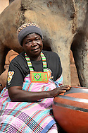 The famous Venda potter, Rebecca Matibe sits in her garden with one of her sculptures behind her and one of her traditional pots beside her. Limpopo, South Africa