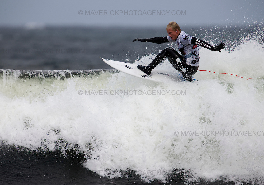 The worlds top surfers compete in the Annual O'Neil Highland Open at the famous surf break Thurso East on the north shore Scotland.  Pictured Adam Melling from Australia, with earplugs to ward off the cold, floats over the top of a Thurso East wave.