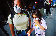 "22 SEPTEMBER 2011 - NEW YORK, NY: A woman and her daughter with dust masks look at the wreckage of the World Trade Center from a vantage point on Liberty Street in lower Manhattan near ""Ground Zero"" of the World Trade Center complex after the WTC terrorist attack, Sept. 22, 2001. More than 2,900 people were killed when terrorists crashed two airliners into the towers on Sept. 11, 2001. Everything for miles around the WTC was covered in dust and ash when the 110 story tall towers collapsed.  PHOTO BY JACK KURTZ"
