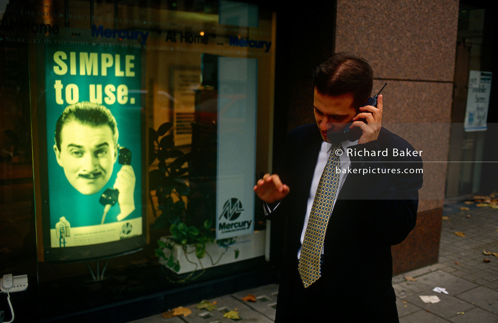 In front of an ad for Mercury, the 90s mobile phone network provider, a city worker uses his mobile phone in a London street.  Actor Harry Enfield was the face of the media campaign on tv and in print to help promote the young industry, still then an expensive accessory for the ordinary Briton. Mercury Communications, was a national telephone company in the United Kingdom, formed in 1981 as a subsidiary of Cable & Wireless to challenge the monopoly of British Telecom (BT). Mercury was the first competitor to BT, and although it proved only moderately successful at challenging their dominance, it was to set the path for new communication companies to attempt the same. In 1997, Mercury ceased to exist as a brand with its amalgamation into the operations of Cable & Wireless Communications and totally exited from the telecommunications business by 1999.
