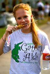 "Stock photo of A ""Gator Aide"" l enjoys some 'gator on a stick during a break at the Texas Gatorfest in Anhuac."