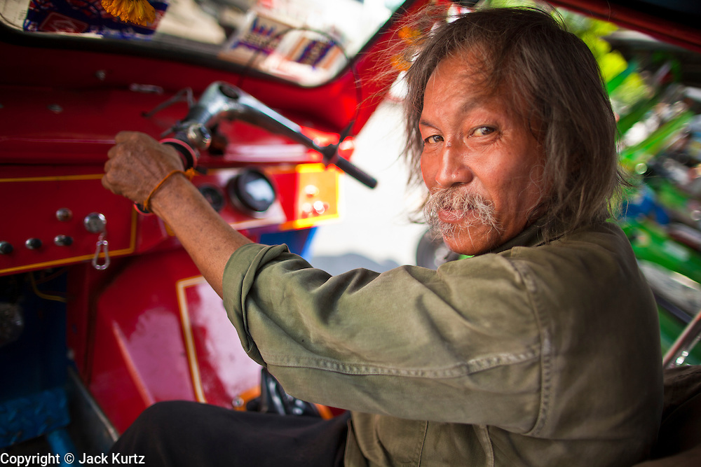 09 JULY 2011 - BANGKOK, THAILAND: A tuk-tuk (three wheeled taxi)  driver in the Chinatown section of Bangkok, Thailand. Chinatown is the entrepreneurial hub of Bangkok, with thousands of family owned businesses selling wholesale merchandise in everything from food like rice, peanuts and meats, to dry goods like toys and shoes.  PHOTO BY JACK KURTZ