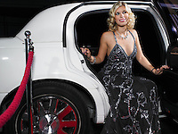 Woman in evening wear getting out of limousine