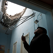 DONETSK, UKRAINE - OCTOBER 19, 2014: A staff member of School 61 in central Donetsk, checks the damaged to the roof of the building hours after it was hit by shellfire presumably shot by the Ukrainian National Guard during fighting for the control of the city's airport area. CREDIT: Paulo Nunes dos Santos