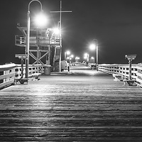 San Clemente pier at night black and white panoramic photo. San Clemente California is a popular beach city in Orange County California in the United States of America. Copyright ⓒ 2017 Paul Velgos with All Rights Reserved.
