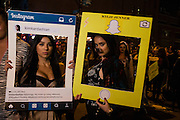 "New York, NY - 31 October 2016. A woman behind an Instagram frame with the user name kimkardashian, hastagged ""IWasBornThisWay #MyButts100%real #AndMyBoobsToo #retunMyDiamonds is accompanied by a woman in a Snapchat frame with the username Kylie Jenner."