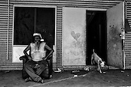 Ralph Karadada sitting outside a house in the One Mile community. <br />