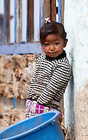 Little Nepali girl standing next to a white wall, Nepal