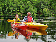 Ashlyn, age 11, and her grandmother take a rest from paddling their kayaks on the Charles River in Newton, Massachusetts