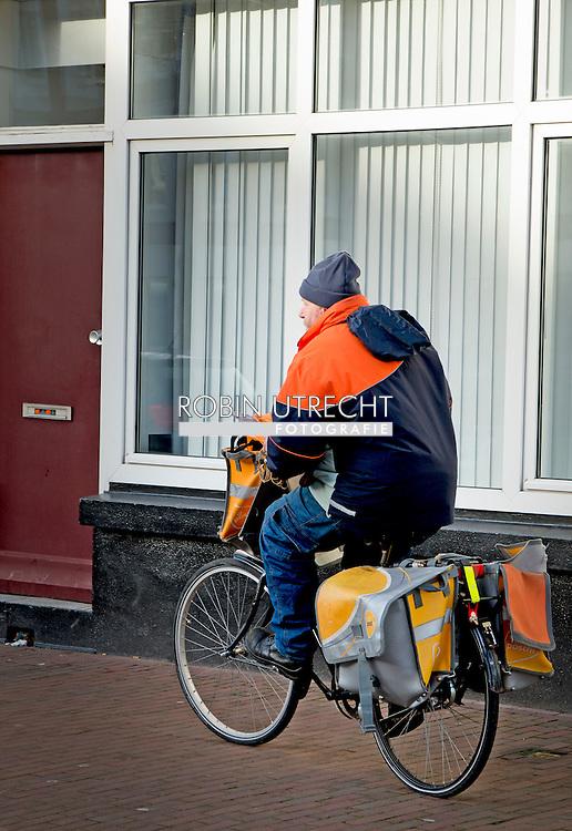 ROTTERDAM - Een postbode in actie op de fiets tijdens zijn werk.  Postbodes gaan de strijd aan met overlast. PostNL wil zijn tienduizenden bezorgers inzetten als 'oren en ogen' van de wijk. Het is de bedoeling dat ze bij het bezorgen van brieven en paketten gemeentes alarmeren over rotzooi op straat. Met foto's  kunnen ze bijvoorbeeld wijzen op overvolle vuilcontainers.  COPYRIGHT ROBIN UTRECHT