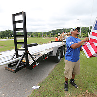 Joshua Patterson begins hanging new American flag on the newly installed flag poles in front of the Vietnam Memorial at Veterans Park in Tupelo.