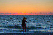 Woman photographing the sunset on Captiva Island in Florida, USA